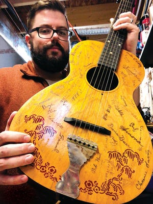 Lucas Weidner poses with the beautiful old acoustic guitar he painstakingly restored. A Cherry Ridge native, Lucas was given the 1935 Supertone Parlor model as a gift. It was purchased at an estate sale back in the 1990s and just oozes local history with more than 60 signatures carved into its body.