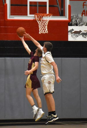 Oppenheim-Ephratah-St. Johnsville Wolf Owen Feagles (right) tries to block a layup attempt by Fonda-Fultonville Brave Jackson Cusack during the second quarter of Thursday's game.