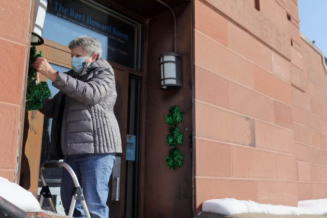 Barbara Bonnett, a volunteer at the Des Moines County Heritage Museum, takes advantage of the sunny weather Friday and changes out Valentine's Day decorations for St. Patrick Day decorations at the Columbia Street entrance to the museum. Bennett was changing the decorations which are up to bring attention to the museum's Columbia Street entrance that houses the Hysterical Treasures pop-up gift shop, which is open from 10 a.m. to 1 p.m. Thursday, Friday and Saturday.