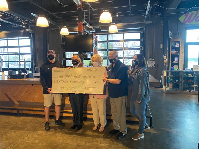 Daniel Courts (from left) of Intuition Ale Works, Eddie Farah of Farah & Farah, Suzie Loving and retired Col. Len Loving of Five Star Veterans Center and Theresa Scordo of the Jacksonville Humane Society take part in Friday's check presentation for the Paws & Stripes program.
