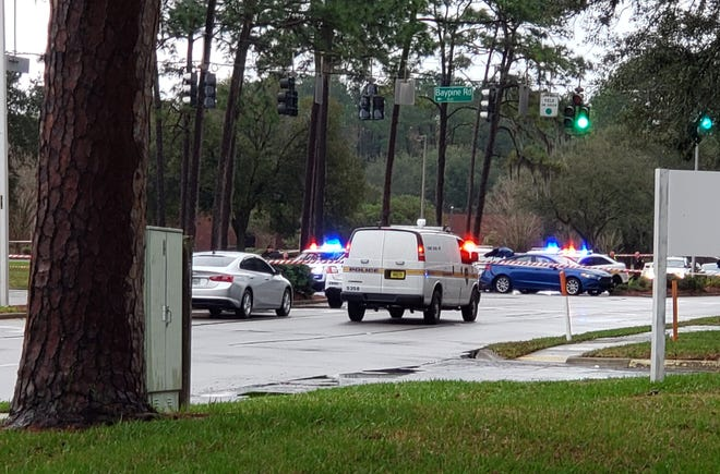 Jacksonville police focus on a blue car at the scene of a shooting death Friday following a Baymeadows Road robbery