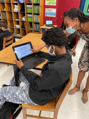 Teacher Cleon Edwards of Joseph Stilwell Military Academy of Leadership, a Duval County middle school, helps student Tyliko Maduro during a Junior Achievement Inspire career exploration program session.