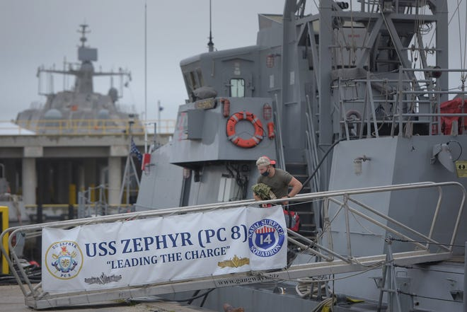 A crew member leaves the USS Zephyr tied up at the pier in the basin of Naval Station Mayport. It and fellow patrol coastal ships USS Shamal and USS Tornado have been decommissioned and were preparing to leave Mayport.