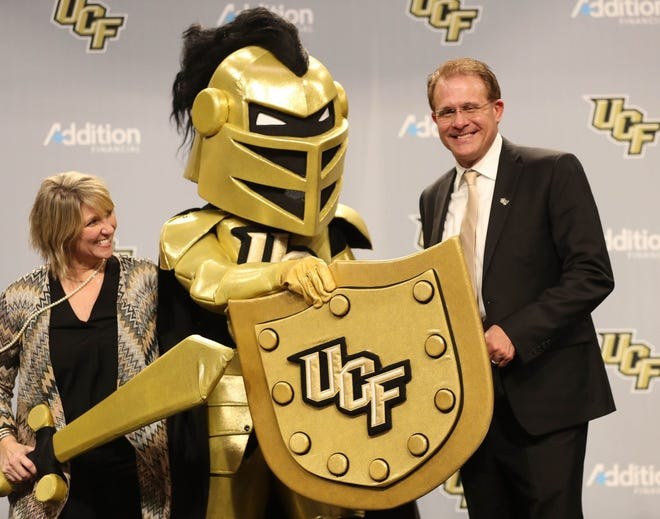 Gus Malzahn (R) and his wife, Kristi, share the stage with UCF mascot Knightro after his introduction as the Knights' head football coach on Monday. The hire of the ex-Auburn coach was a bold move that should benefit UCF in the long run.