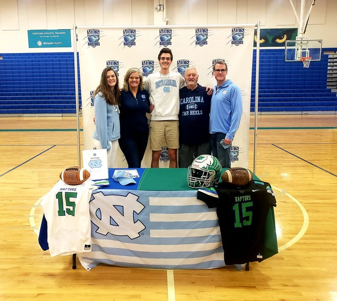 Mountain Island Charter football player Todd Pledger takes a picture with family members after signing with the University of North Carolina at Chapel Hill.