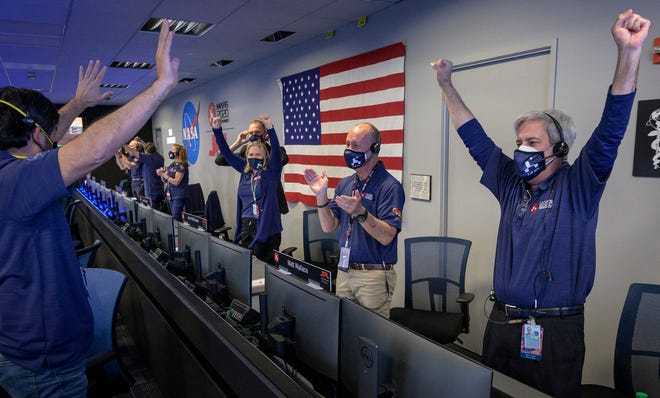 In this handout image provided by NASA, members of NASA's Perseverance rover team react in mission control after receiving confirmation the spacecraft successfully touched down on Mars, Feb. 18, 2021, at NASA's Jet Propulsion Laboratory in La Canada Flintridge, Ca.