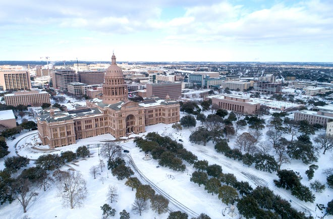The Texas Capitol grounds are covered in snow on Monday, Feb. 15, 2021, in Austin, Texas. A total of 40,969 Austin Energy customers were still without power as of 2 p.m. Thursday, down from 220,000 earlier in the week.
