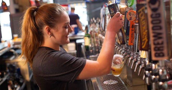 A bartender pours drinks at Big E's Sports Grill. The business announced it would close its doors indefinitely at three locations, including one in downtown Holland and two in Grand Rapids.
