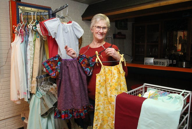 "Sharon Mockridge shows the mission dresses she sews for children in third world countries in her ""Sewing Cave"" on Thursday, Feb. 18, 2021, at her home in Freeport."