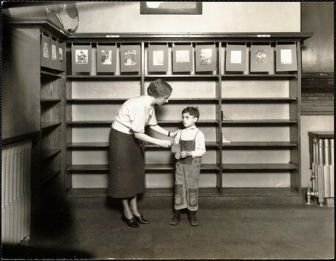 A North End librarian is with a little boy during Fine Cancellation Week in October 1932.