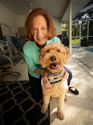 Claudia Slate poses with Teddy, her goldendoodle. Slate has received both doses of a COVID-19. She got the shots at Lakeland Regional Health Medical Center, where she volunteers with Teddy, a therapy dog. Slate said she worried about getting COVID-19 mainly because she lives with her 90-year-old mother-in-law.