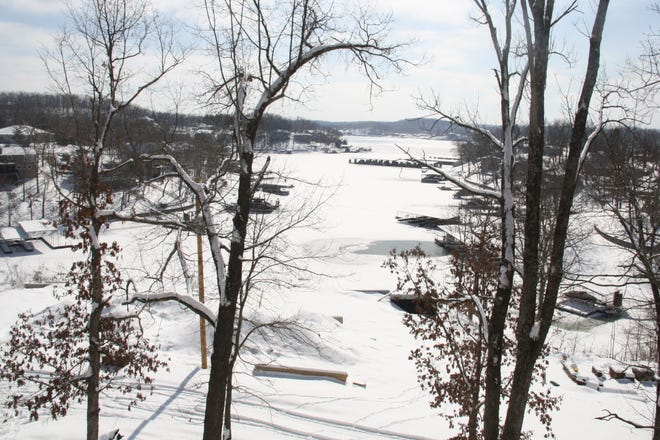 Frozen-over Lake of the Ozarks through a line of trees.