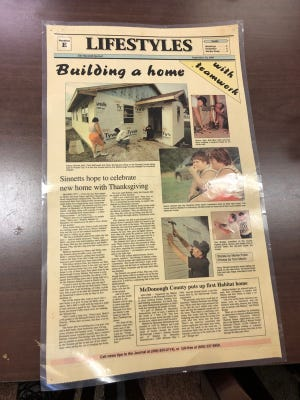 A laminated page from the Sept. 14, 1997 edition of the Macomb Journal shows the Sinnett's home being built. The Sinnett home was the first built by Habitat for Humanity in McDonough County.