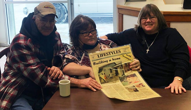 Left to right: Perry, Holly and Nancy Sinnett hold a story that was written about their home as it was being built by Habitat for Humanity in 1997. The Sinnetts are celebrating paying off the mortgage on the home this year.