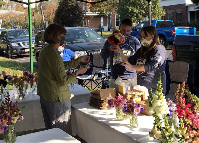 Madison Nolley, right, assists her customers with their fresh cut flower purchases last fall at the Hamilton Farmers Market. Madison recently received a $1,000 Farm Credit Supervised Agricultural Experience grant to help her raise and sell her own dahlias.