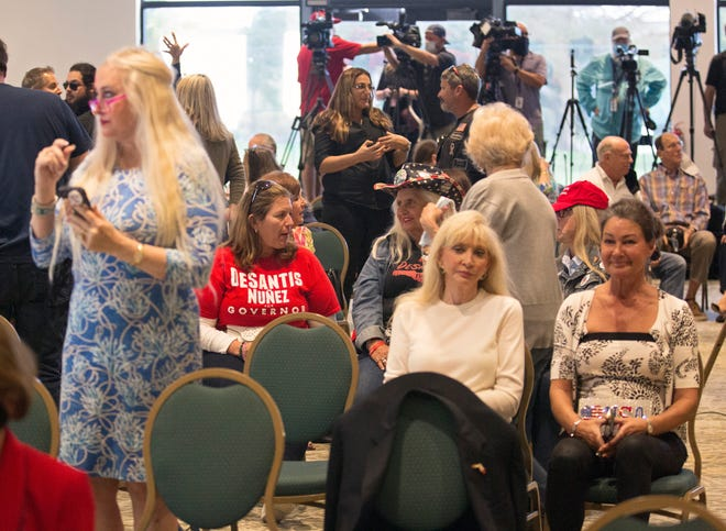 Unmasked supporters of Gov. Ron DeSantis crowd a conference room at the Hilton Airport Palm Beach in West Palm Beach in violation of county ordinances as they await his arrival Friday, February 19, 2021.