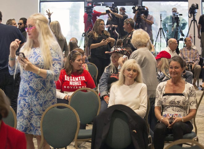 Unmasked supporters of Florida Gov. Ron DeSantis crowd a conference room as they await his arrival at the Hilton Airport Palm Beach in West Palm Beach, Fla., Friday, Feb. 19, 2021, in violation of county ordinances requiring face masks to prevent the spread of the coronavirus. (Lannis Waters/The Palm Beach Post via AP)