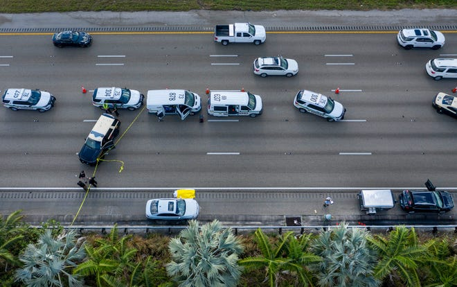 Police investigate the scene where a motorist was shot and killed by another on the shoulder of I95 north, south of Donald Ross Road Friday in Jupiter.