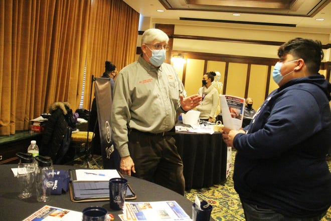 Chris Roberts, maintenance training supervisor with Tyson, visits with Perry High School senior Miguel Sierra during a career fair on Thursday, Feb. 18 at the Hotel Pattee.