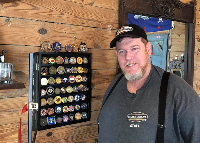 Three Brothers' Distillery co-owner David Reavis stands beside his challenge coin collection on display in Disputanta, Va. on Nov. 21, 2020.