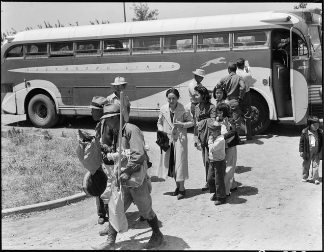 A group of Japanese Americans that had been evacuated from their homes in the Lodi area are checked by officials as they get off the bus May 19, 1942; that day, eight busloads arrived at the temporary Japanese War Relocation Center at the San Joaquin County Fairgrounds. Though they had little need for household equipment in this new life, many are seen bringing in new brooms.