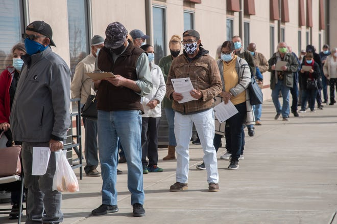 People stand in line to receive a COVID-19 vaccination at the Progressive Community Church in south Stockton on Thursday.