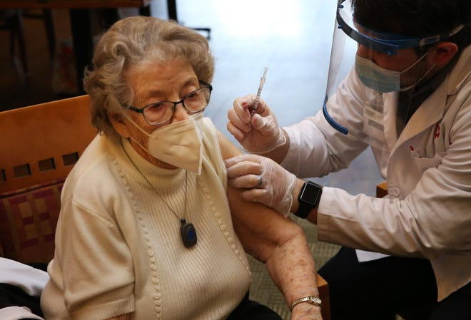 "Bernice Homan, left, receives her second COVID-19 vaccination from pharmacist Victor Rojo during a clinic at Willamette Oaks Retirement Home in Eugene Friday Feb. 19, 2021. It was painless enough she asked the doctor ""All done?"" after the second shot."