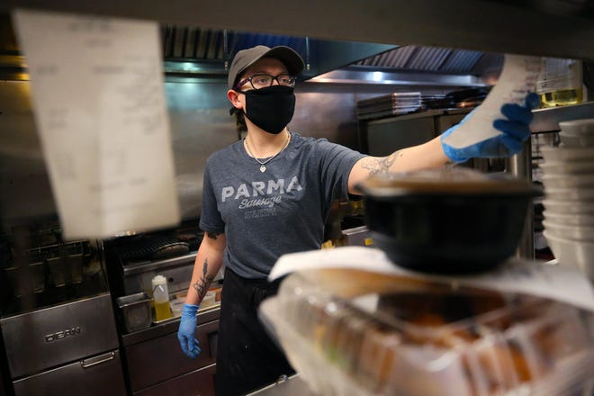 Crave line cook Riley Gibson checks tickets for delivery-only orders in Akron.