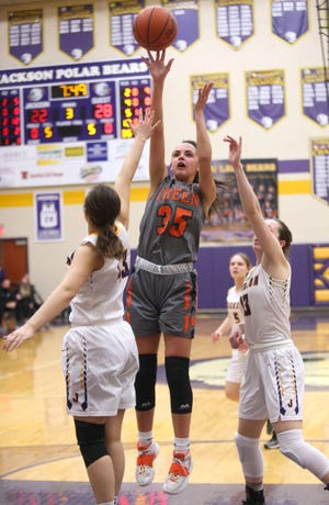 Green's Alyssa Ziehler (35) takes a shot while being defended by Jackson's Kylie Hawke (left) and Emma Dretke (right) during Thursday's Division i sectional final game.