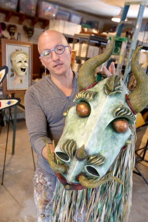 Jonathan Becker displays a sea creature mask he created using a combination of Japanese, Celtic and Chinese elements, in his Canton home workshop.