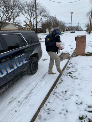 An officer with the Dublin Police Department helps deliver warm meals for Meals on Wheels of Erath County earlier this week.