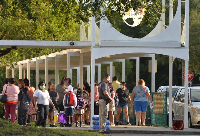 Parents line up with their children at Samoset Elementary School for the first day of classes in Manatee County in August. Cases of COVID-19 within Sarasota and Manatee county schools continued to taper off this week, after hitting a peak in January.