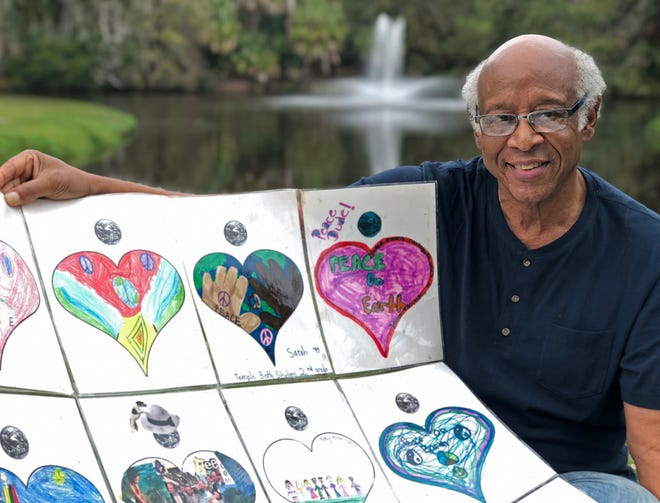 David Gittens, 82, shows part of his Only Hearts Art/Peace Project from 1999, illustrated by children.