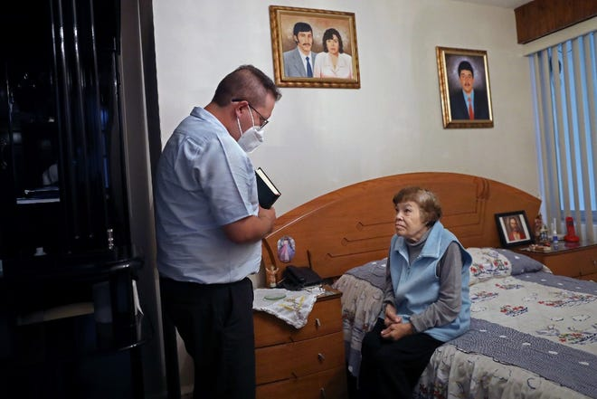 The Rev. Julio Cesar Ponce, 30, makes a house call to offer the sacrament of the Anointing of the Sick and the eucharist to Guadalupe Patino Velazquez, 72, at her home on Aug. 14 in Ciudad Nezahualcoyotl, Mexico. A portrait of Patino Velazquez's husband, who died in February of this year, hangs in her bedroom.