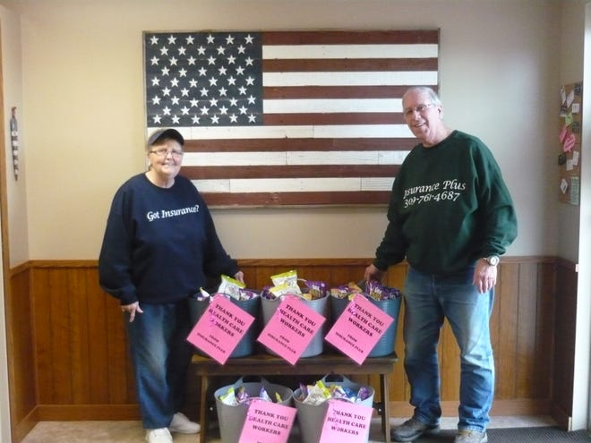 """Insurance Plus's Andre and Philip DeSmit, parents of owner Jenny DeSmit Hodges, show the care packages donated by the company recently delivered to local nursing homes. Jenny said the business saw a need and acted: """"We felt like we had to do something. As we have all tried to get back to normalcy, these long-term care facilities continue to take a hit. I have several customers who are employed at these facilities and they are tired, but not willing to give up. Our hopes are to supply some small snacks and keep the staff energized in order to continue caring for our seniors."""