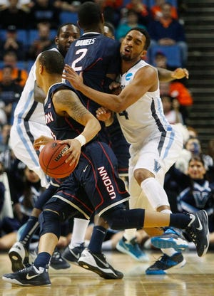 Villanova's Darrun Hilliard II (4) runs into a pick set by Connecticut's DeAndre Daniels (2) as he chases Shabazz Napier during the NCAA tournament game on March 22, 2014.