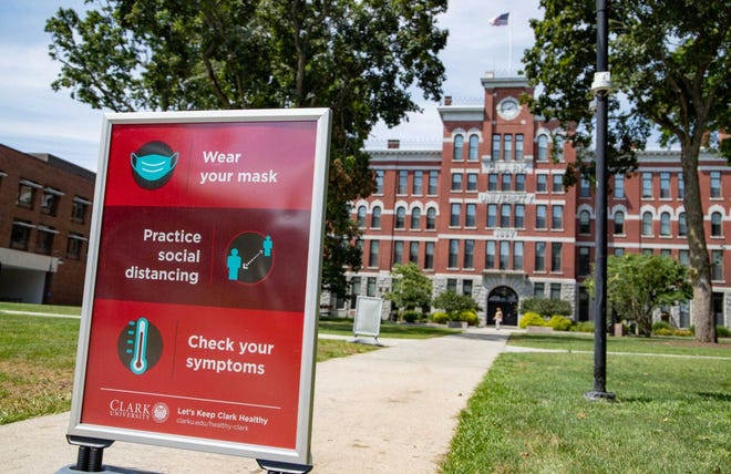 Signs posted around the Clark University campus in Worcester urge the use of face masks, social distancing, and attention to symptoms.
