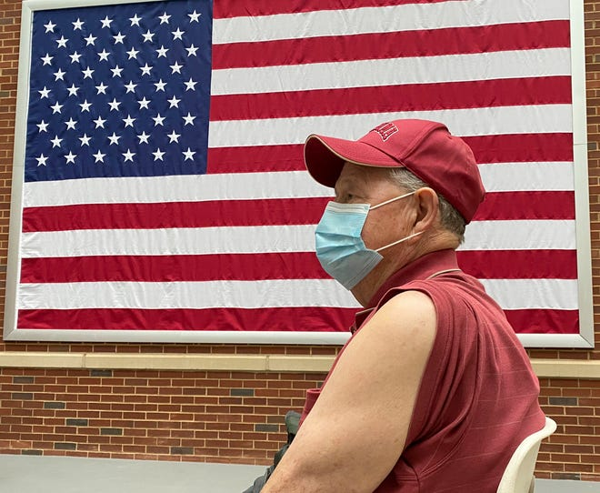 Veterans receive COVID-19 vaccines at the VA Medical Center in Tuscaloosa Wednesday, Jan. 13, 2020. Army veteran John Thomas White waits beneath an American flag to receive the first dose of his vaccination. [Staff Photo/Gary Cosby Jr.]