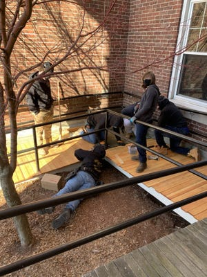Northeast Metro Tech students repair the ramp outside of the Stoneham Fire Department to allow for safer access to the building.