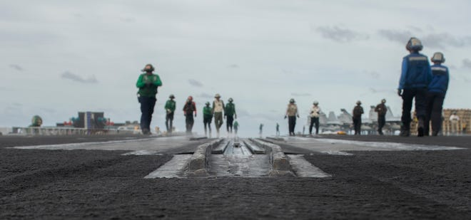 Sailors inspect a catapult on the flight deck of the aircraft carrier USS Nimitz during flight operations Feb. 12. The carrier, which departed its homeport of Bremerton in the spring, is on the last legs of its journey home.