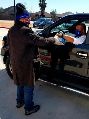 Mehmet Gurbuz, principal of the School of Science and Technology Bayshore Campus, hands potato chips to teacher's aide Tony McClain on Friday, Feb. 19, 2021. Gurbuz organized a cookout for his staff in response to the winter storm that affected the Corpus Christi area earlier in the week.