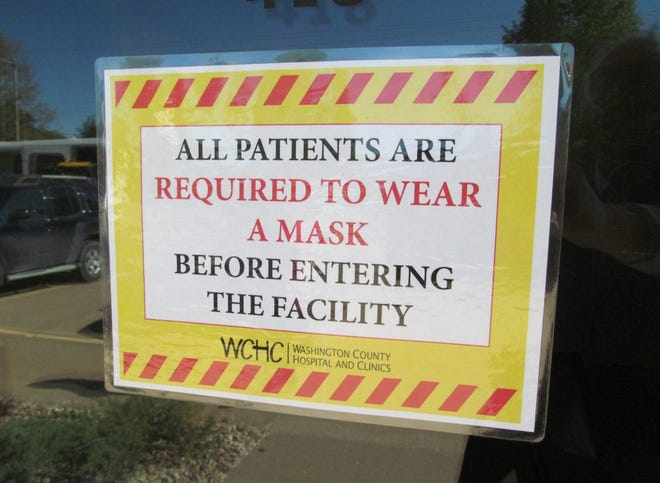 A face mask warning on a clinic door at Washington County Hospital & Clinics on Friday, May 8, 2020. The response Iowa hospitals were giving COVID-19 was in the earlier stages.