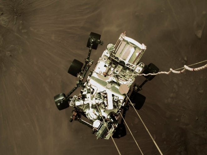 This Thursday, Feb. 18, 2021 photo provided by NASA shows the Perseverance rover lowered towards the surface of Mars during its powered descent.  - 9900f874 9ff3 42fa b519 012e97cfc875 AP21050657094635 - Michigan native's space fascination takes flight with Mars mission