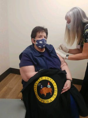 """With a sweater bearing the words """"Little Shell Chippewa Tribe,"""" Linda Watson receives the first dose of the tribe's covid-19 vaccine supply. ()"""