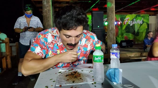 Ricardo Carrazco of the U.S. chomps his way through 100 donne' sali Feb. 13, 2021, to win the hot-pepper eating contest during the 17th Annual Tinian Hot Pepper Festival in San Jose, Tinian.