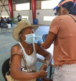 Agat resident Mary Babuta, 62, is injected with the Pfizer-BioNTech COVID-19 vaccine at Agat Gym, Feb. 19, 2021.