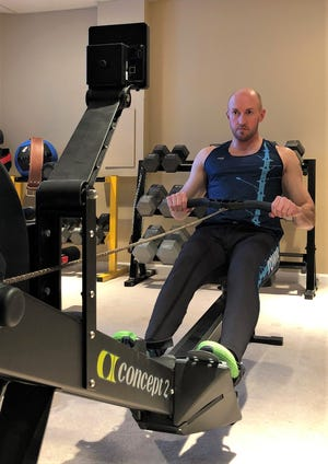 Tyson Whitt, 43, works out on his rowing machine. He's qualified for and will race in two events in the 2021 World Rowing Indoor Championships.