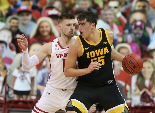 Iowa  center Luka Garza works the ball against Wisconsin forward Micah Potter on Thursday night at the Kohl Center.