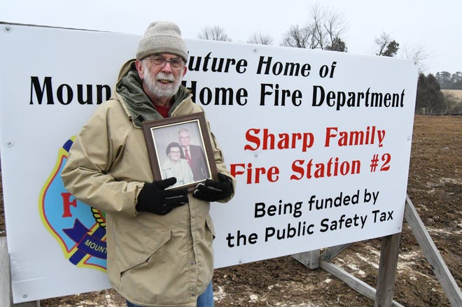 Sonny Sharp holds a photo of his parents, W.E. 'Red' and Margaret Sharp, during a recent visit to the site of the future Sharp Family Fire Station #2.