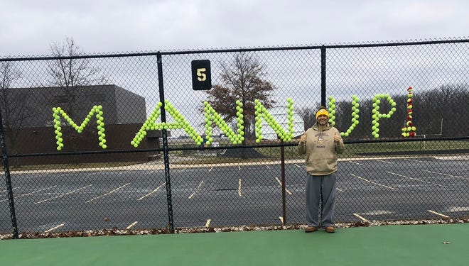 """Reece Mann poses in front of a """"Mann Up"""" message made of tennis balls. The term was coined by Delta Basketball Coach Mark Detweiler."""